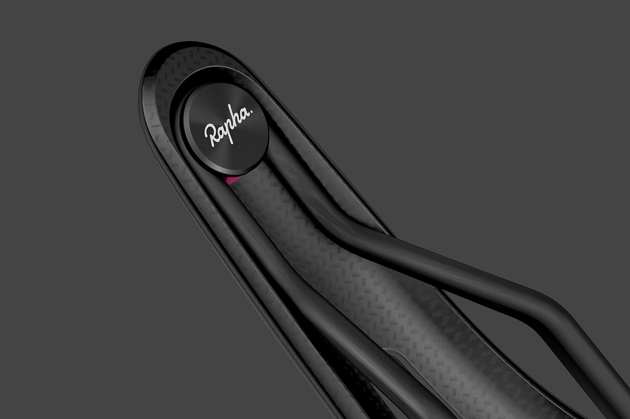 Perspective view of a section of a Rapha Saddle showing the details and logo on the bottom surface, black on a black background.