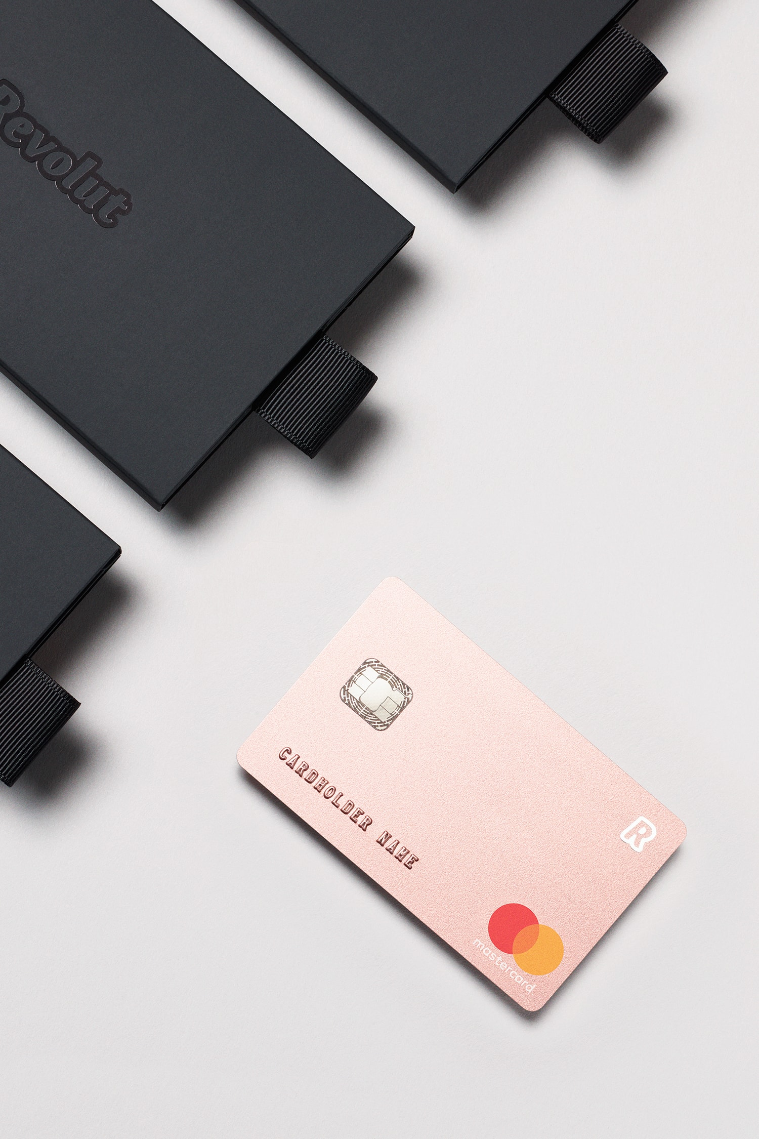 Perspective view of the Revolut Premium bank card in metallic pink beside black packaging.