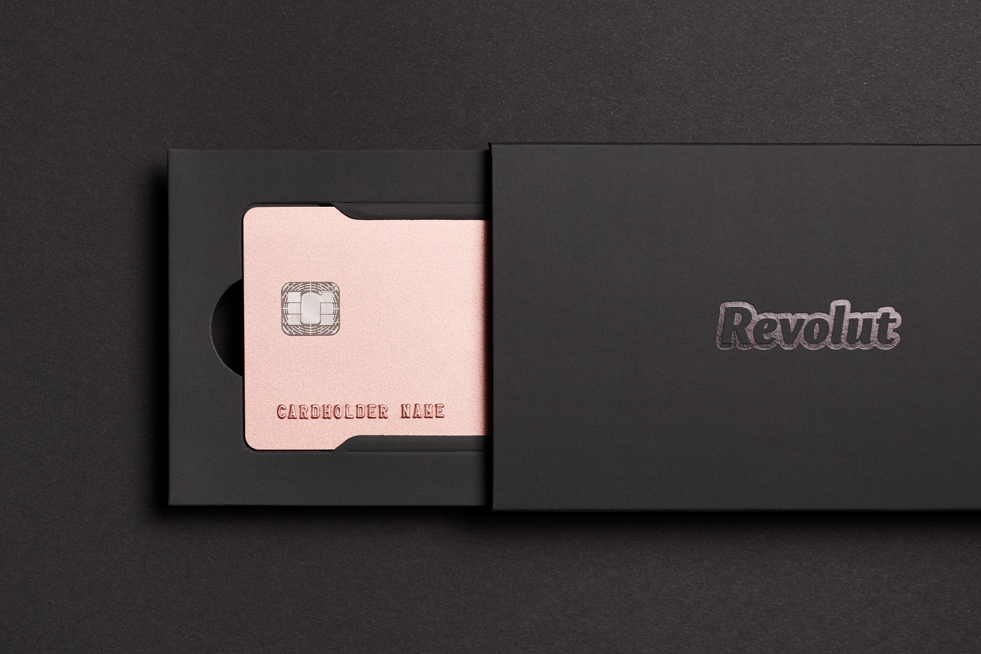 Top view of the Revolut Premium bank card in metallic pink inside black packaging on a black surface.
