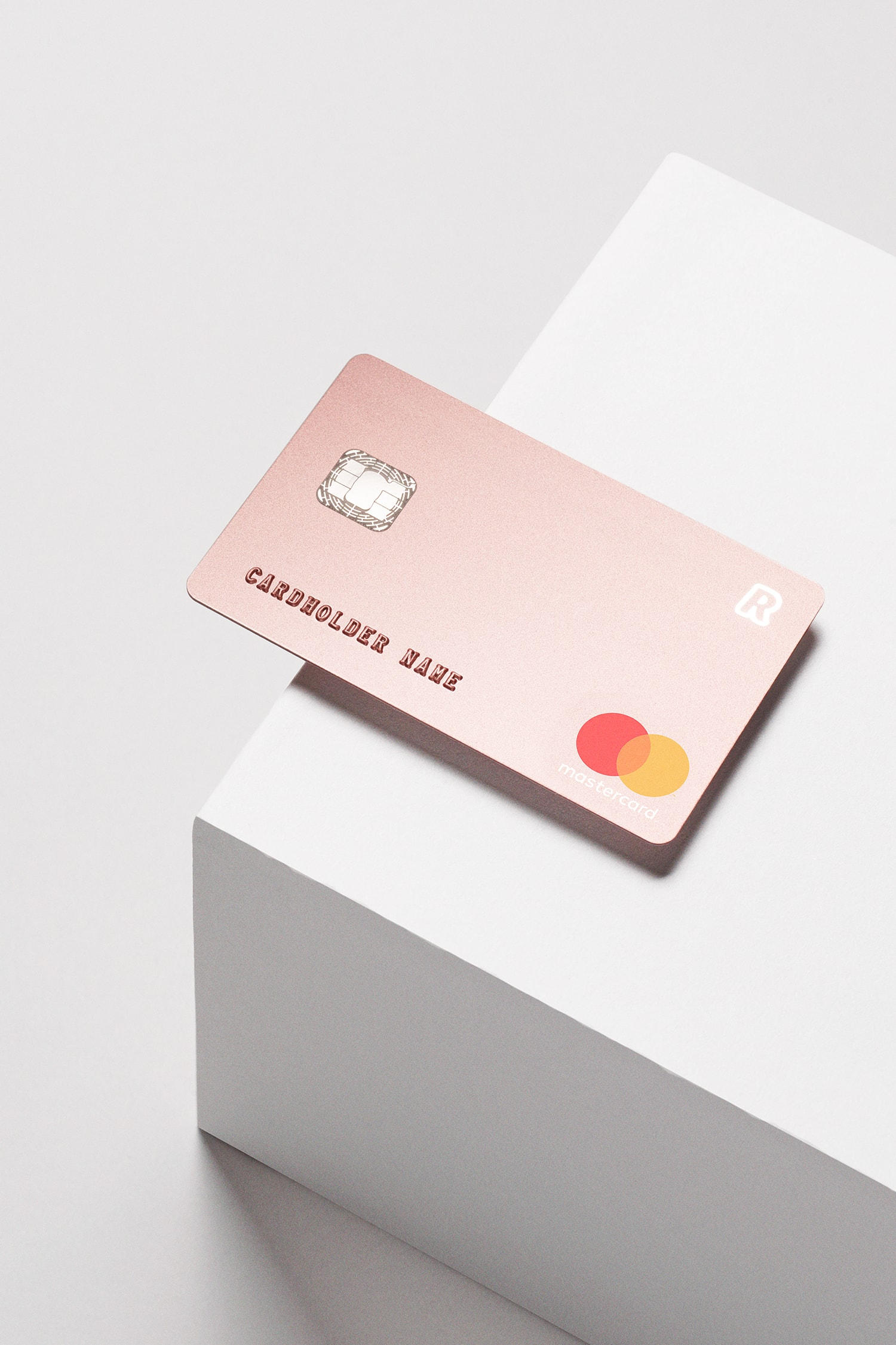 Perspective view of the Revolut premium bank card laid on the edge of a white plinth.