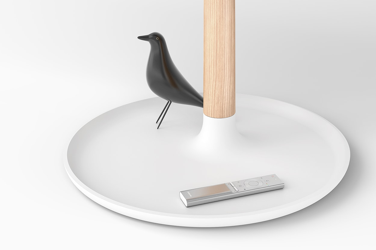 Detail view of the light wood leg and white base. The base is containing a black bird ornament and a silver remote control.