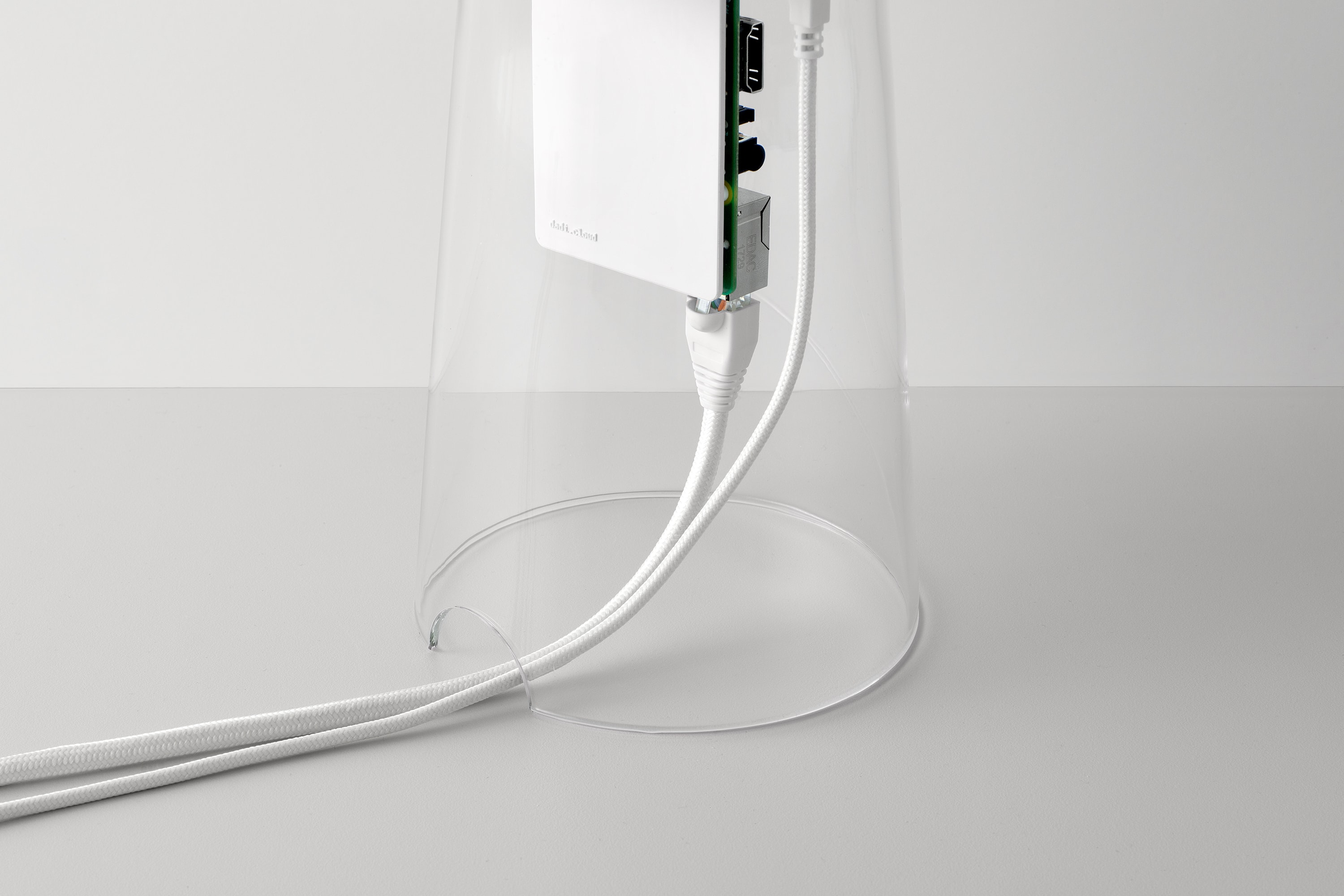 Perspective view of part of the DADI Founding Node. The components include; a glass casing, a plastic component which has a Raspberry Pi circuit board mounted on to it. There are cables connected to the Raspberry Pi which exit the glass casing through a small semi-circle shaped gap.