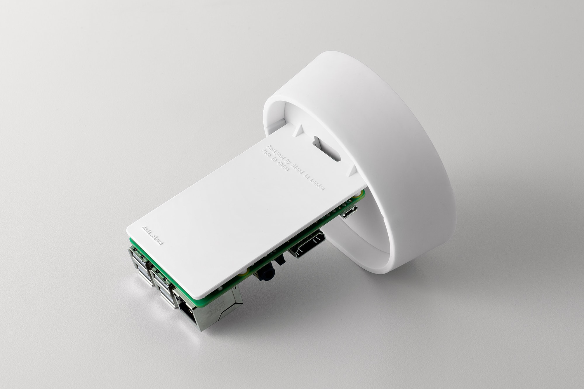 Perspective view of the top of the DADI Founding Node. The image shows a white silicone top, attached to the top is a plastic component which has a Raspberry Pi circuit board mounted on to it.