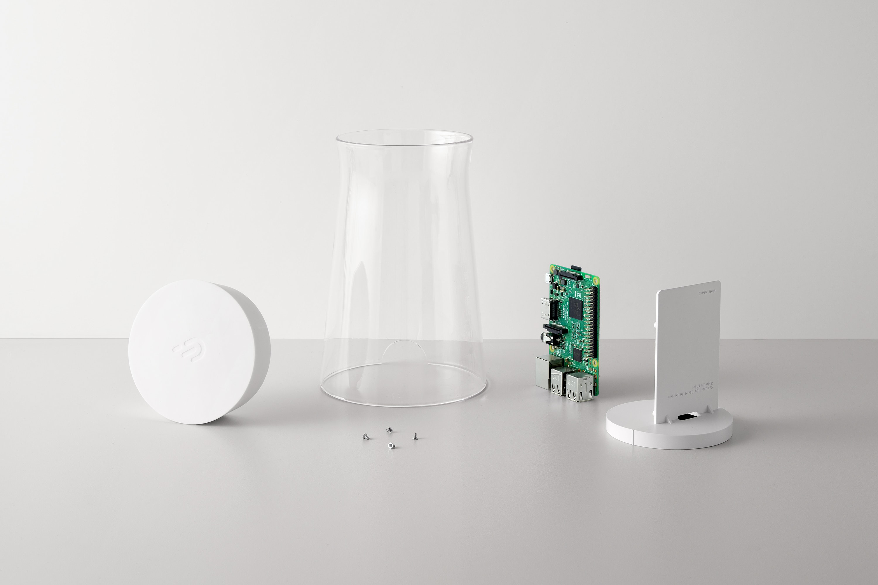 Front view of the DADI Founding Node deconstructed. The components include; a glass casing with a white silicone top, a plastic mounting, a Raspberry Pi circuit board and four small silver screws on a grey surface.