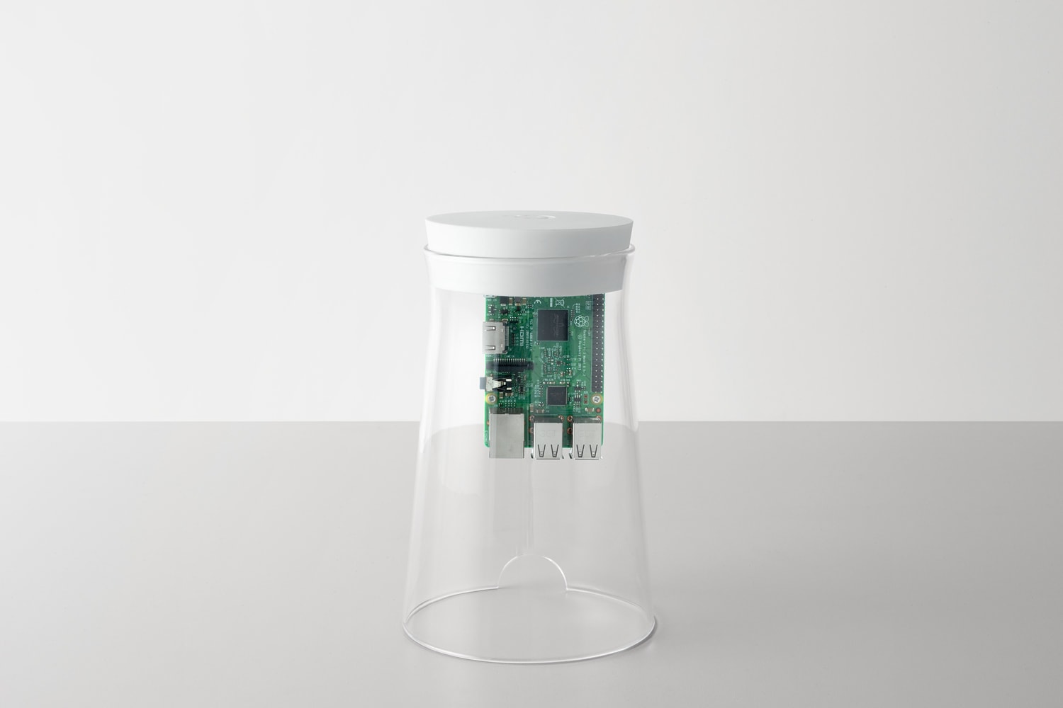 Front view of the DADI Founding Node. The components include; a glass casing with a white silicone top, attached to the top is a plastic component which has a Raspberry Pi circuit board mounted on to it.