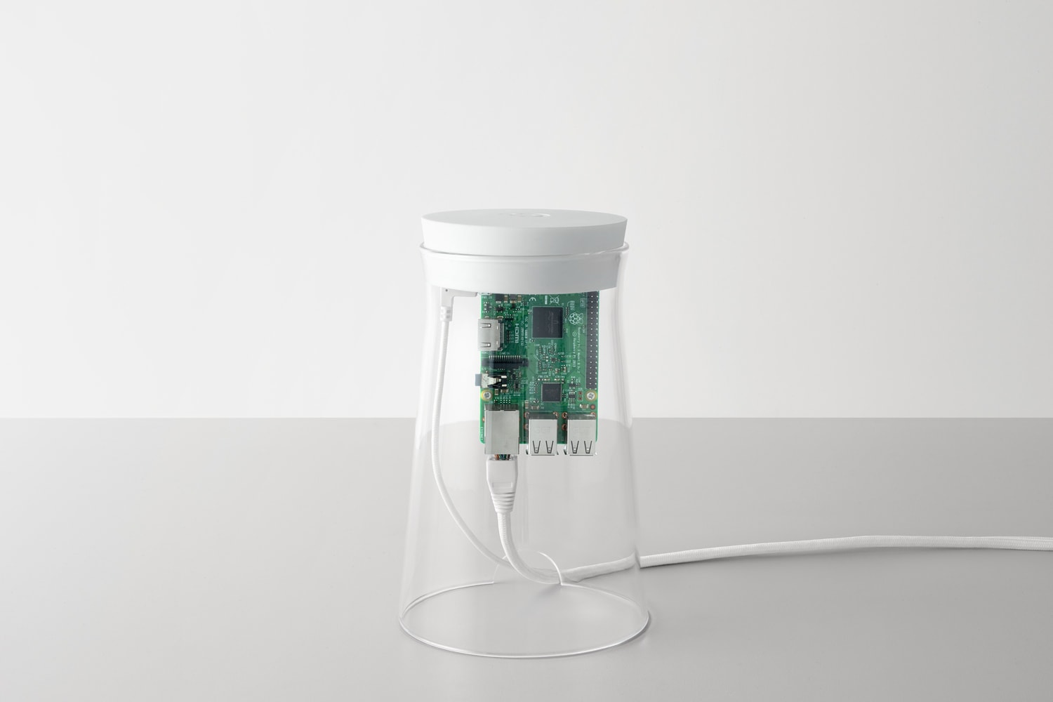 Front view of the DADI Founding Node. The components include; a glass casing with a white silicone top, attached to the top is a plastic component which has a Raspberry Pi circuit board mounted on to it. There are cables connected to the Raspberry Pi which exit the glass casing through a small semi-circle shaped gap.