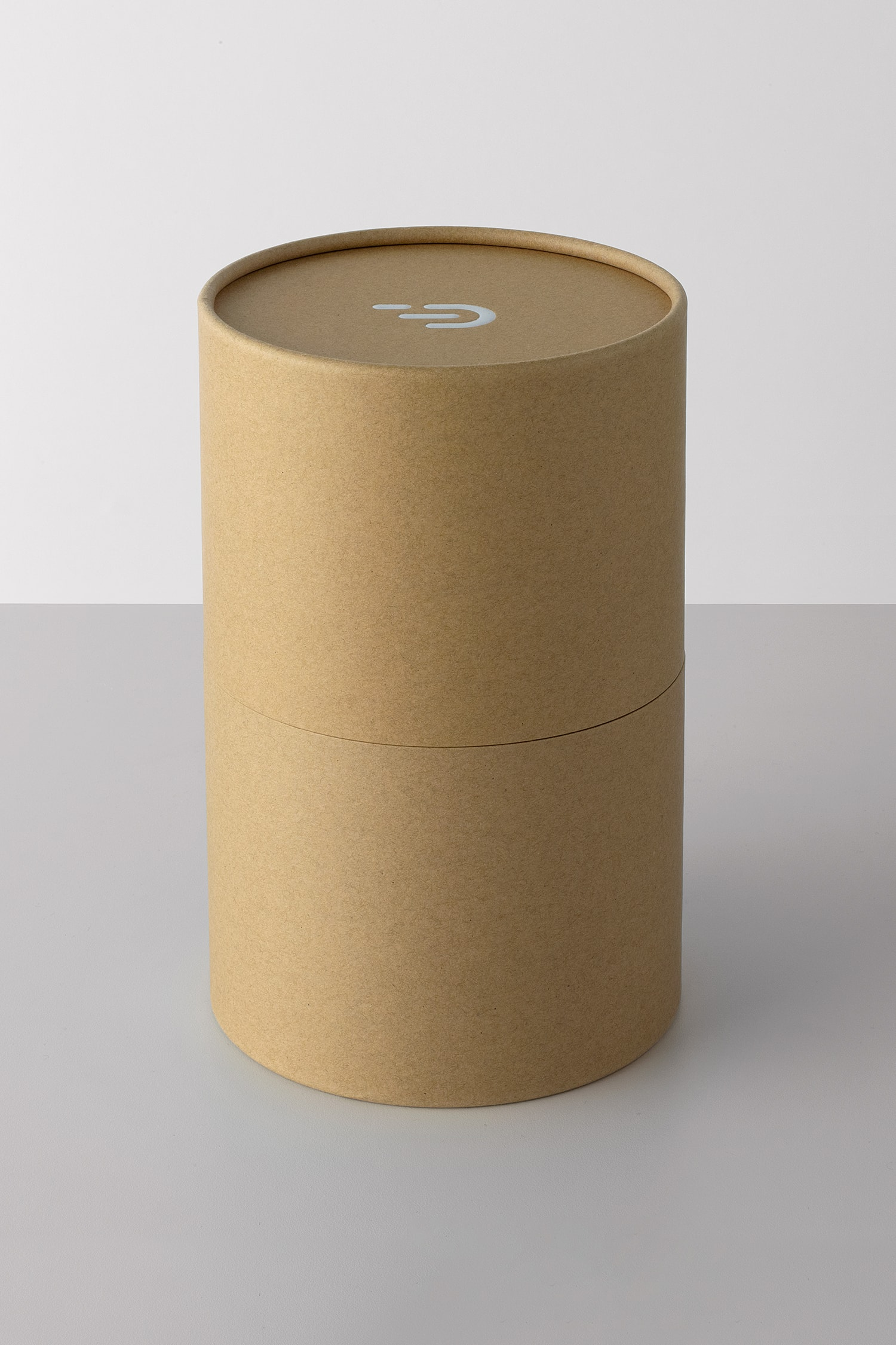 Front view of the DADI Founding Node packaging. The packaging is a cardboard cylinder with the DADI logo printed in white on the top surface.