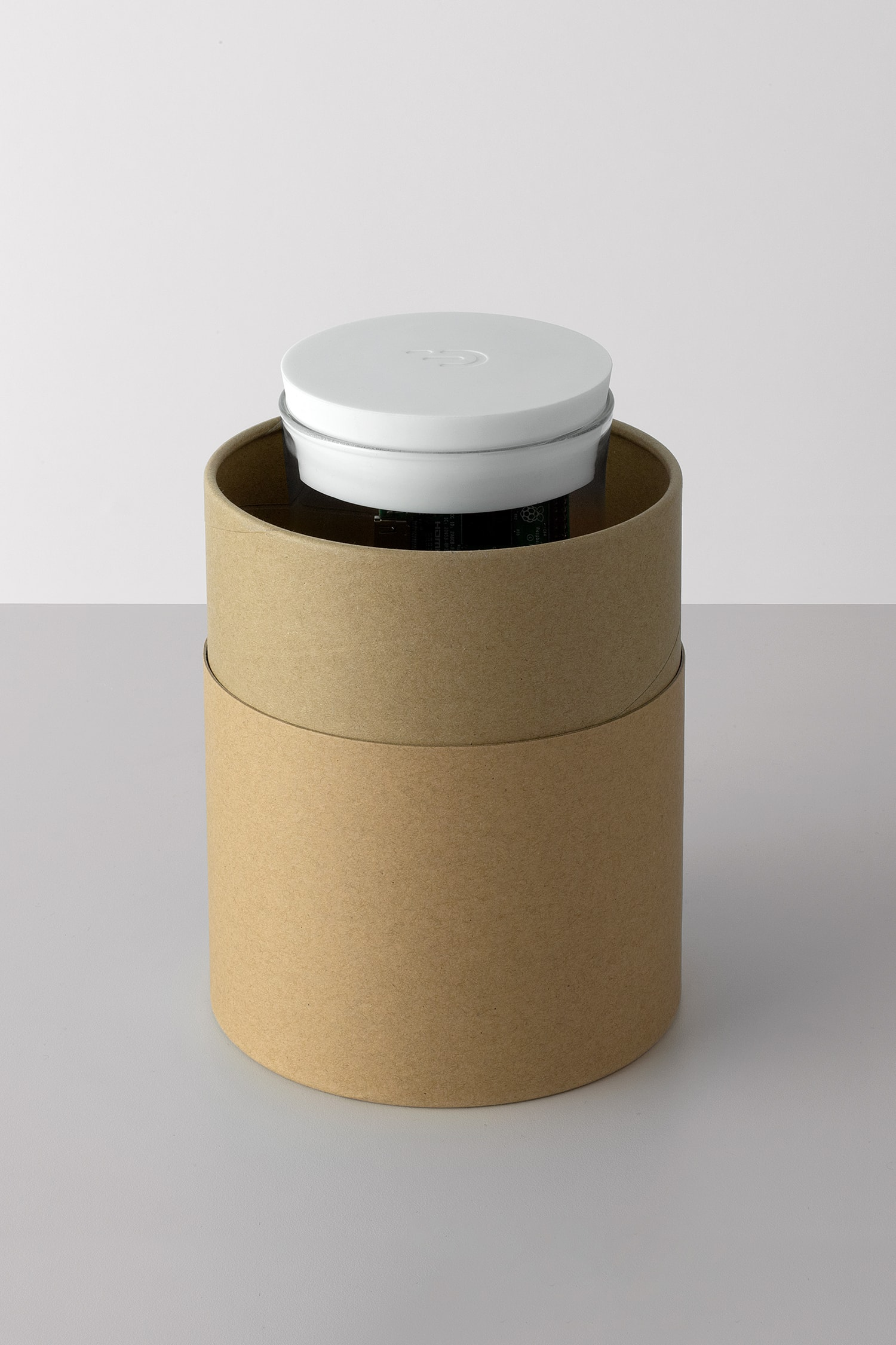 Front view of the DADI Founding Node in packaging. The pacaging is a cardboard cylinder with the lid off. Inside we can see the top of the DADI Founding Node and the logo embossed into the silicone top.