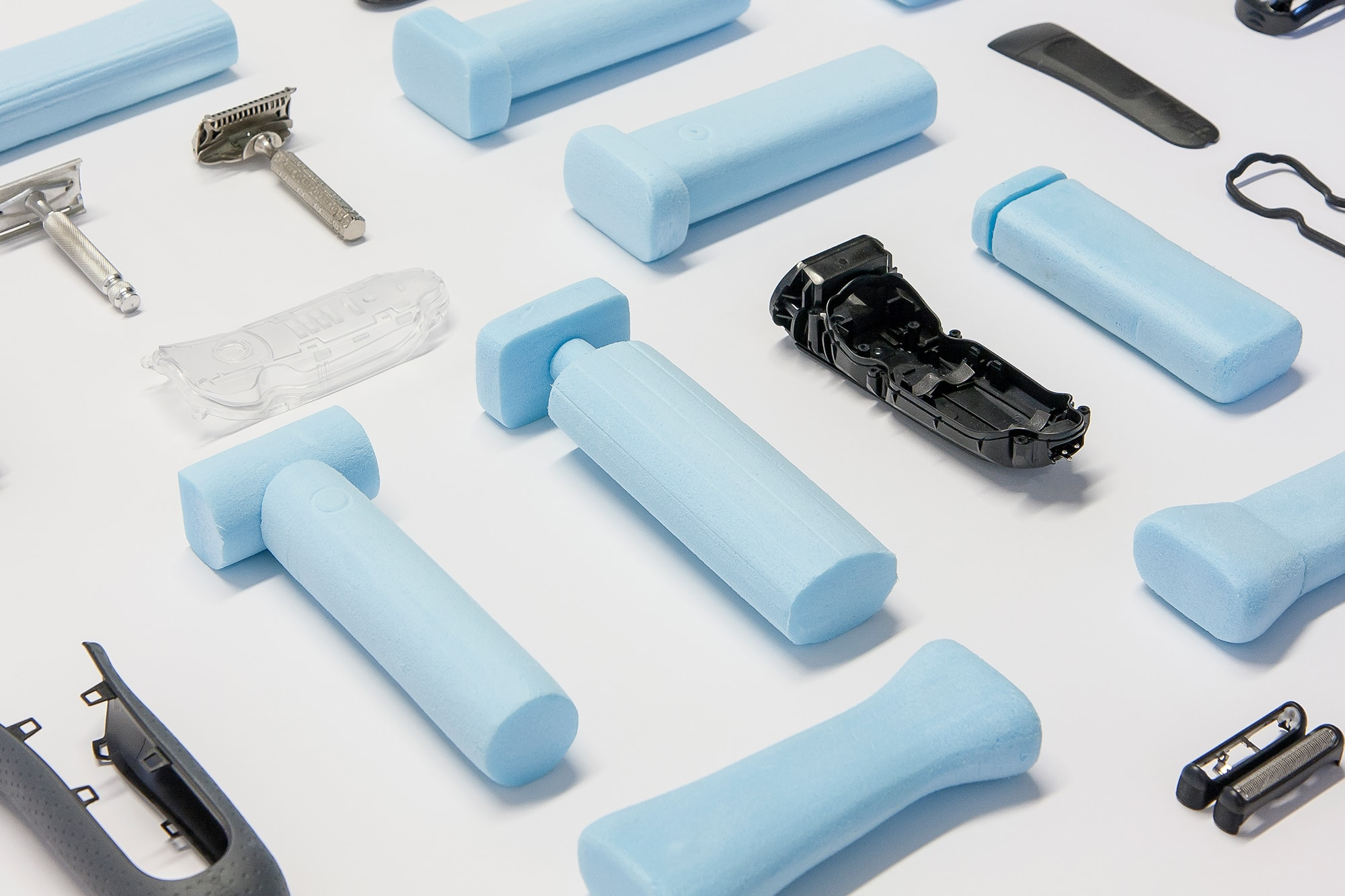 Blue foam models and dismantled shavers laid out on a white background.