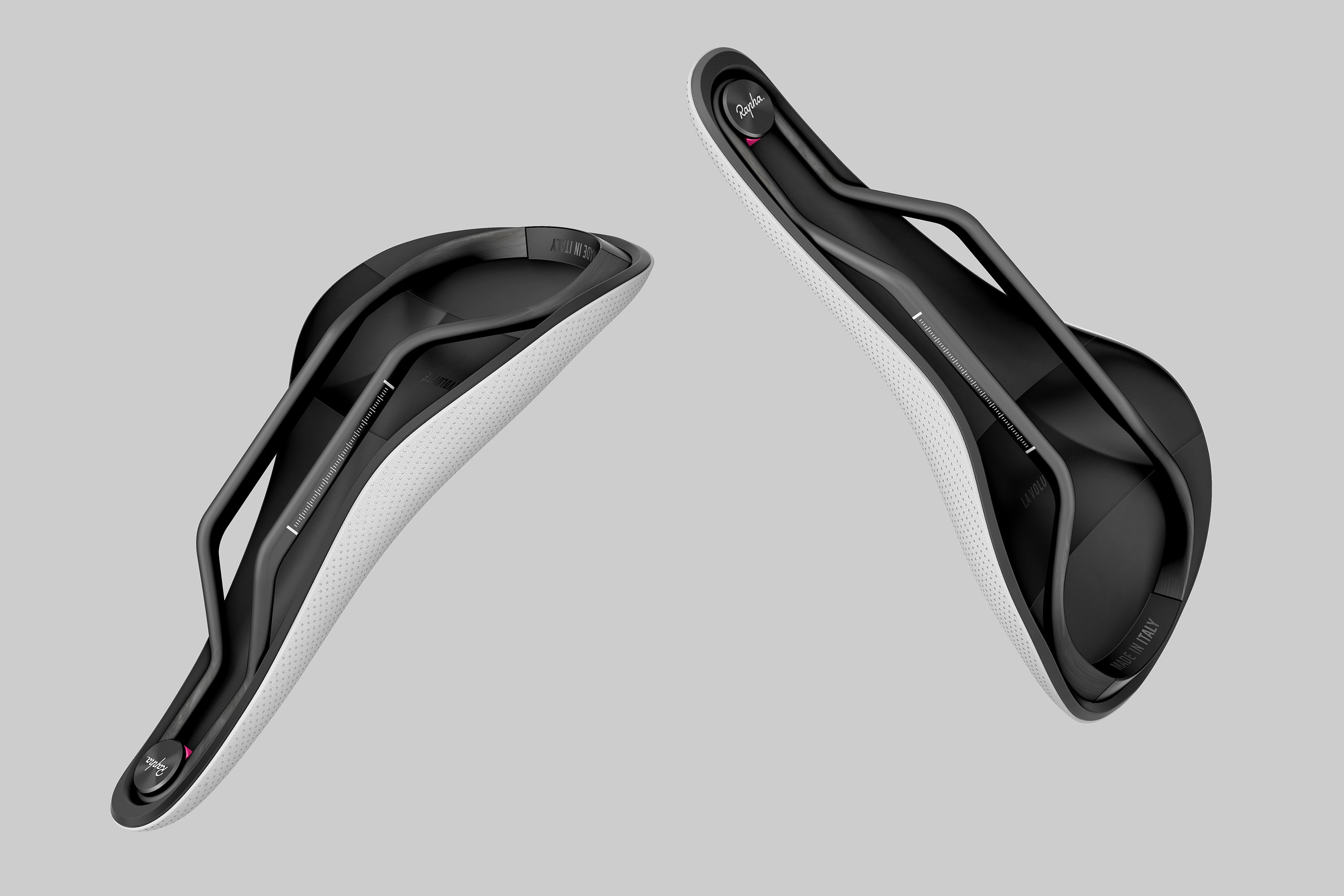 Perspective view of two Rapha Saddles floating against a light grey background. The image shows the underside of the saddles with the Rapha logo and parts of the white top surface.