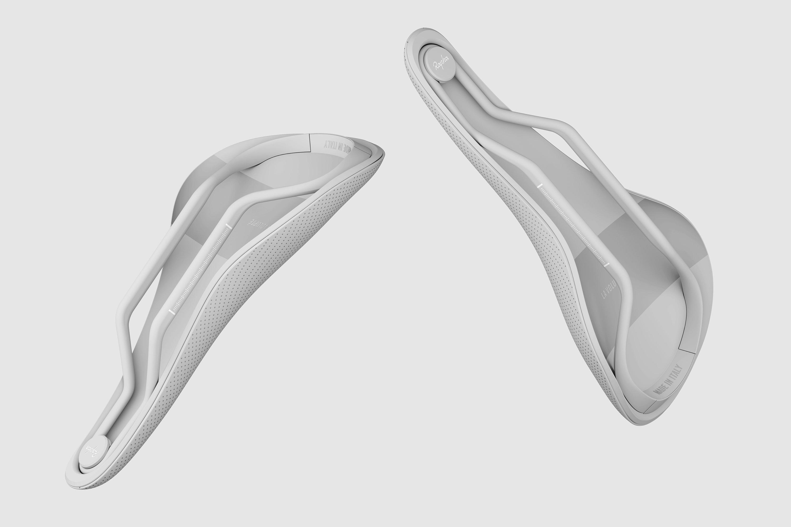 A greyscale render showing a perspective view of two Rapha Saddles floating against a light grey background. The image shows the underside of the saddles with the Rapha logo and parts of the top surface.