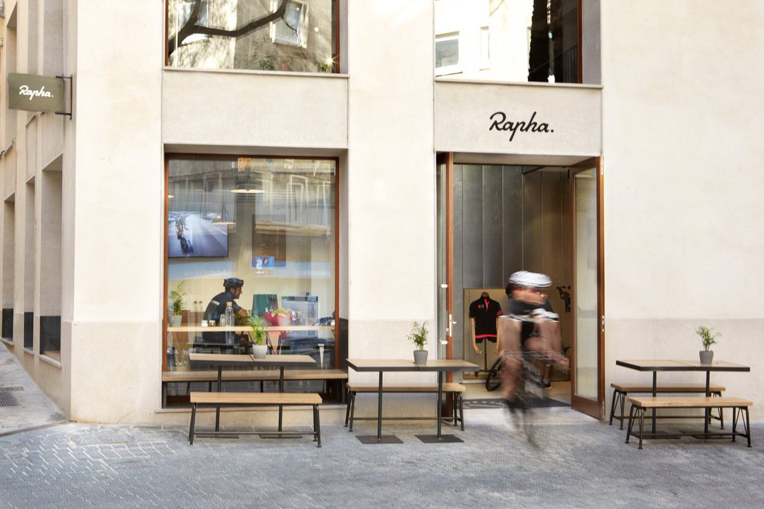 Exterior of the Rapha Clubhouse in Mallorca. A cyclist is inside and another is riding nearby.