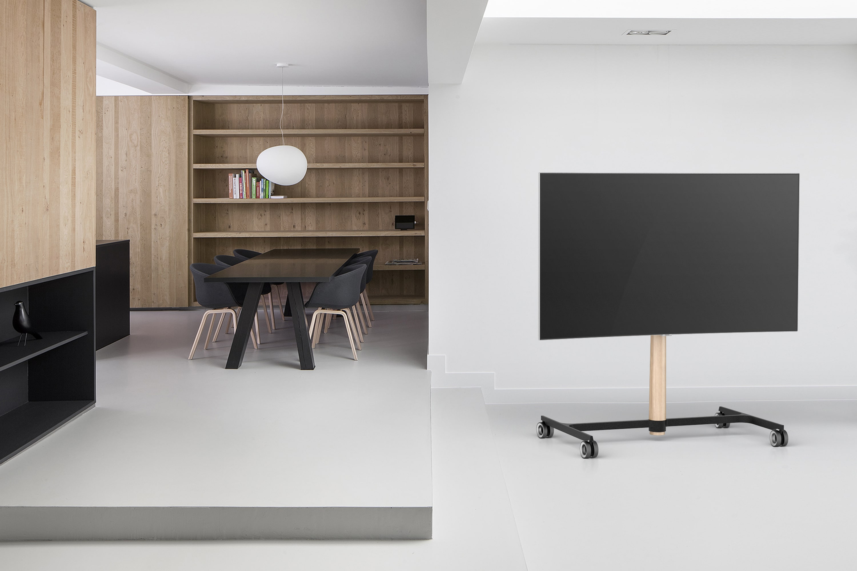 Television stand in context. Light wood leg and a black base in professional setting.