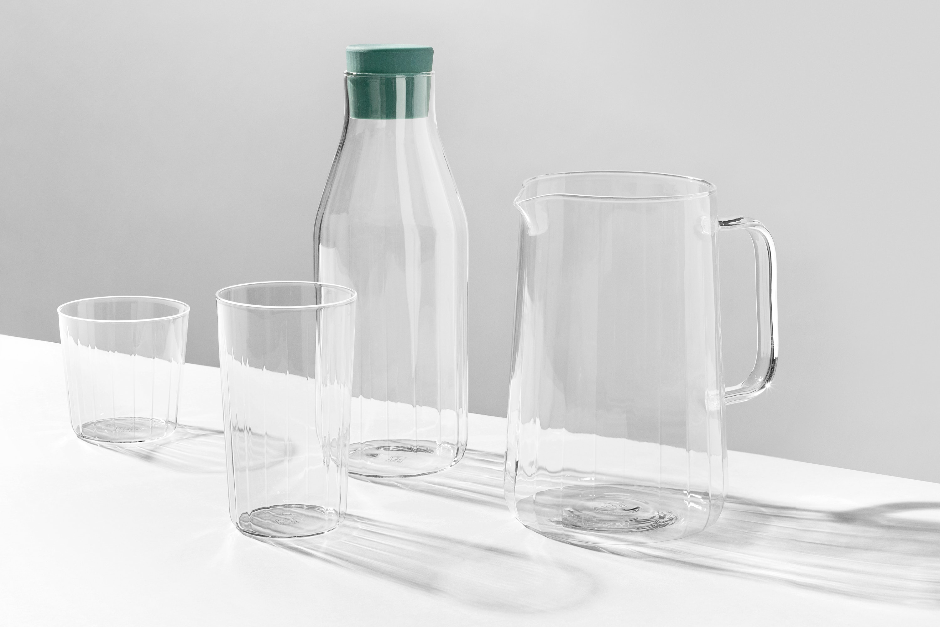 Rivington Glassware tumbler, high ball, jug and carafe on a white surface. The lighting is causing the shadows to be stretched across the surface, emphasising the facets.