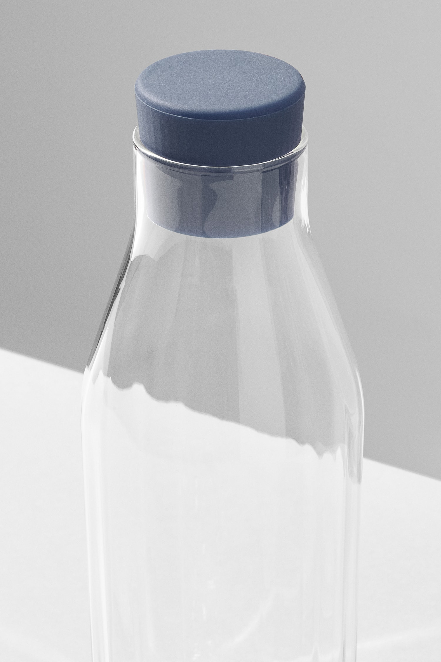 Perspective view of the top of the Rivington Glassware carafe showing the facets, blue stopper.