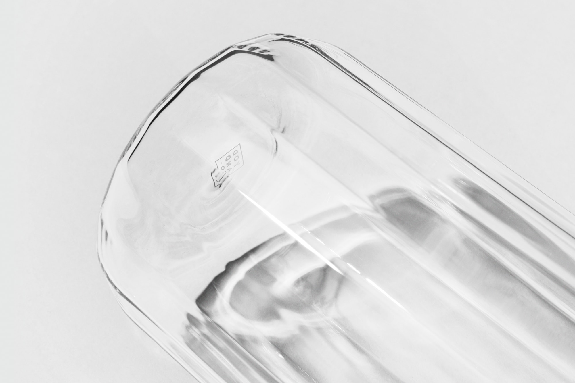 Base of the Rivington Glassware carafe against a light grey background. The facets and branding are shown in more detail.