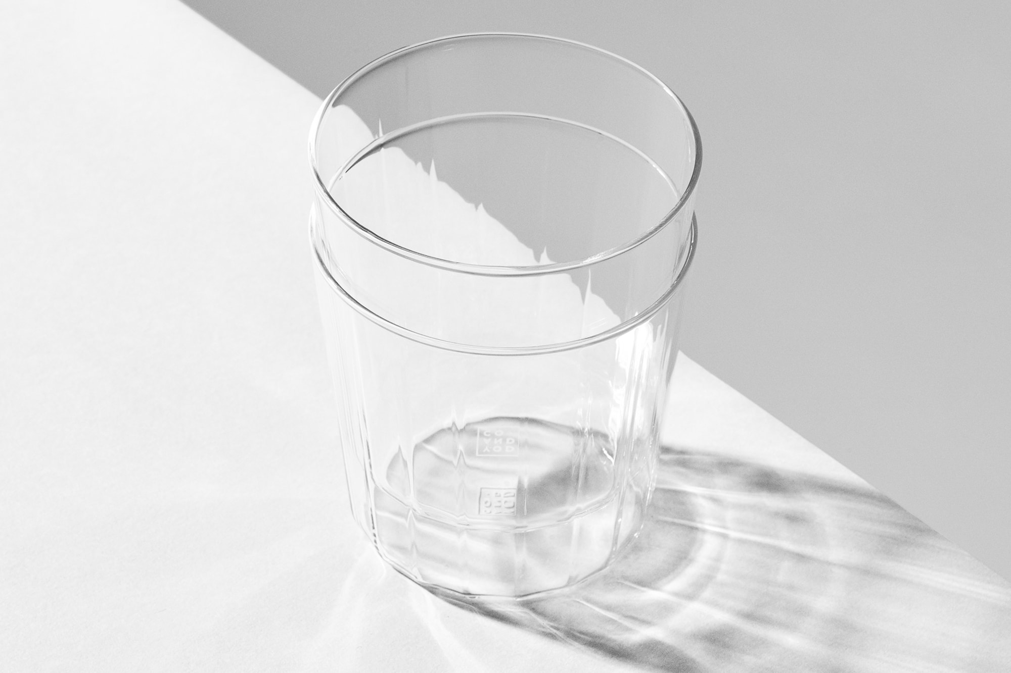 Two Rivington Glassware tumblers stacked on a white surface casting a shadow. The subtle facets can be seen in the distortion of the edge of the surface.