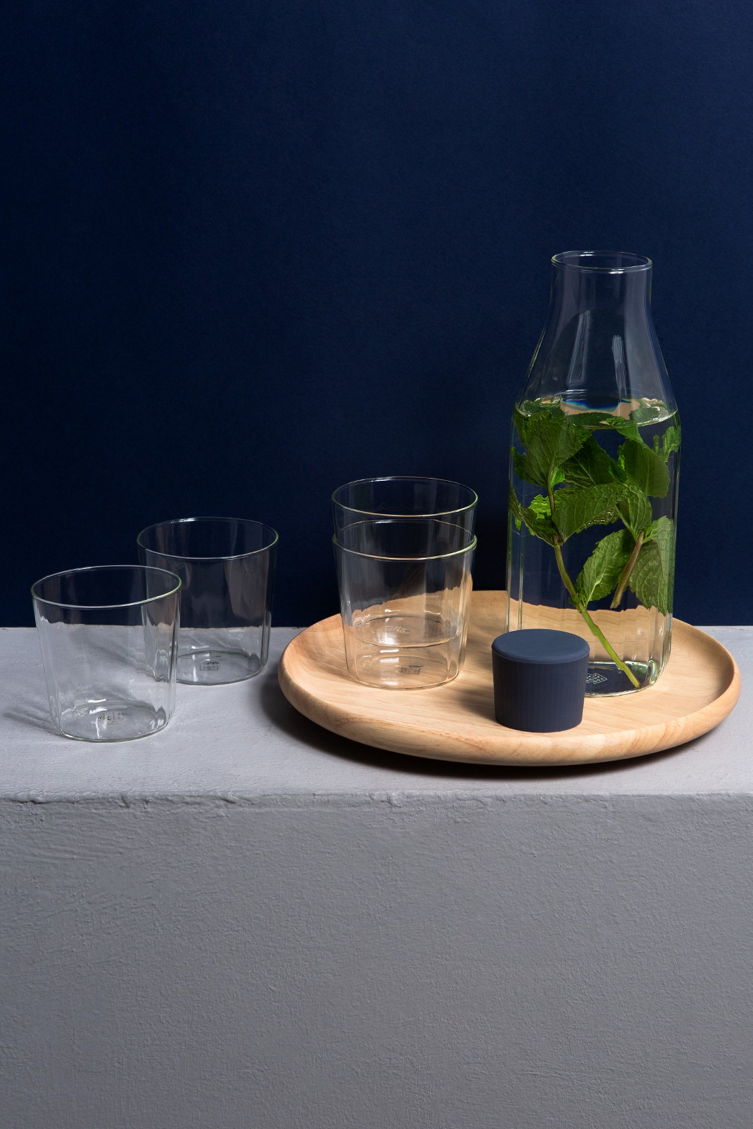 Front view of the Rivington Glassware collection, four tumblers, two of which are stacked and a carafe with its blue silicone stopper off and beside it. Inside the carafe is water and mint leaves. The carafe and stacked tumblers are on a wooden plate. White surface and dark blue background.