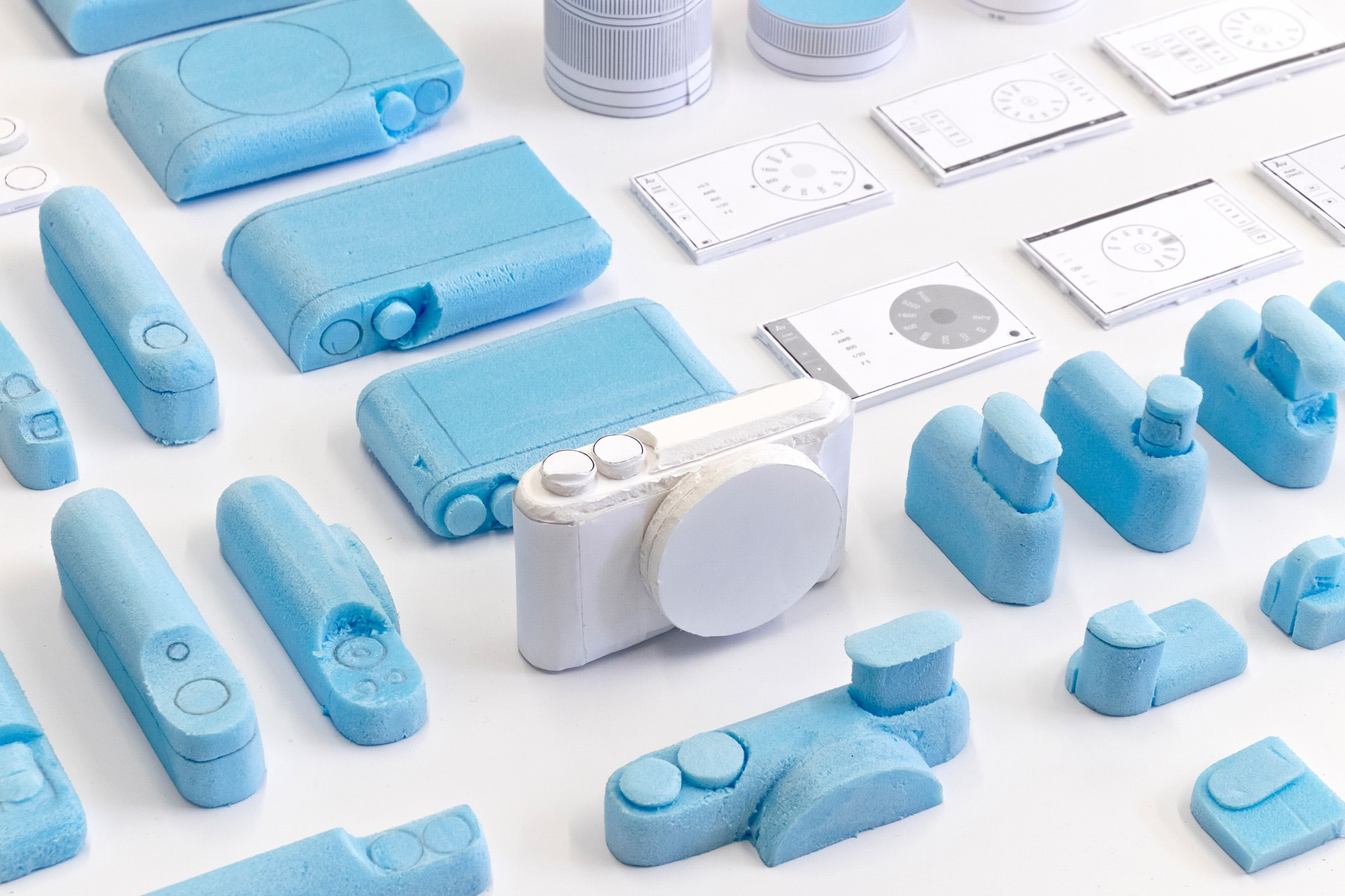 Prototypes of the Segment camera. Iterations of different components are shown in blue foam with a complete white foam model in the centre.