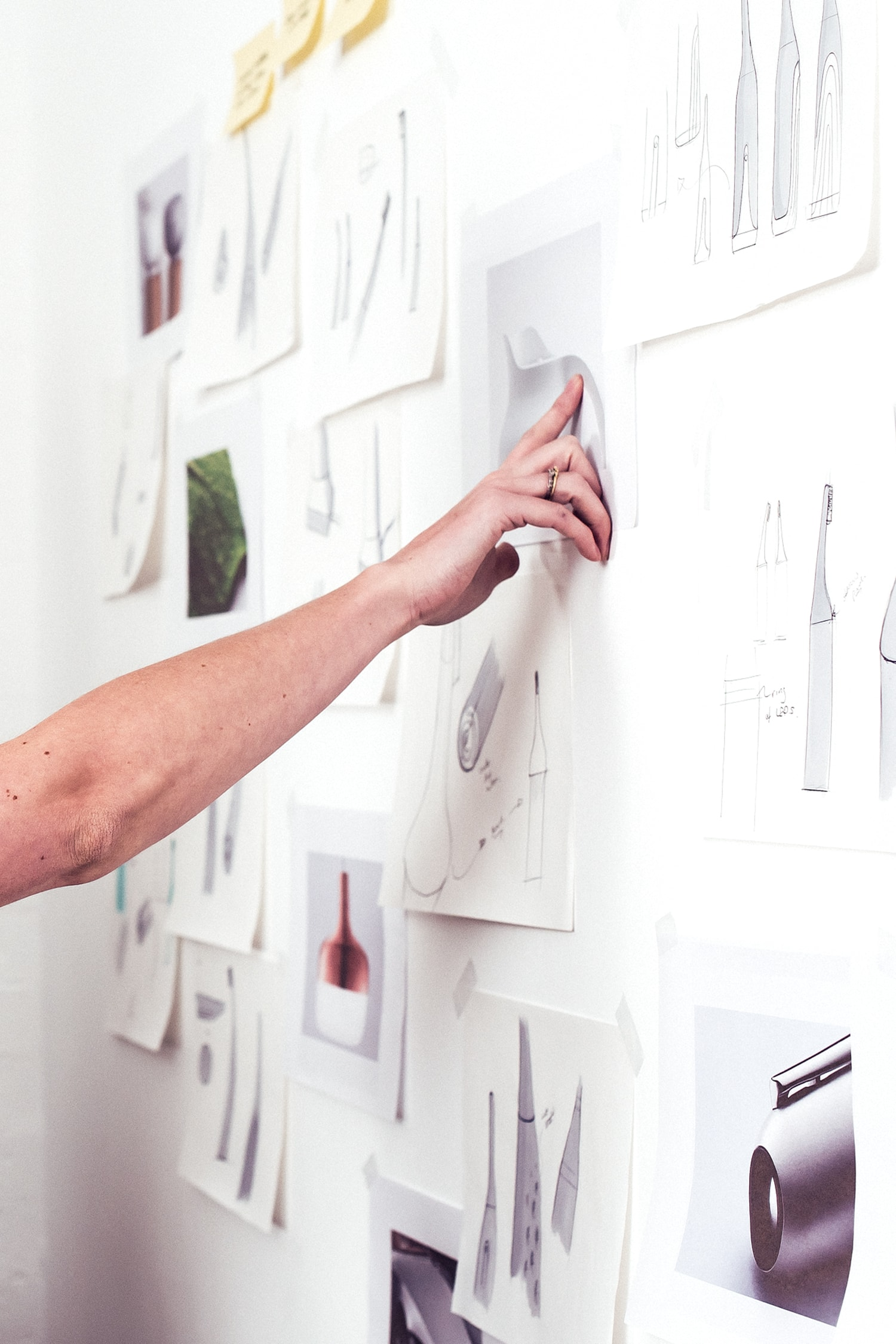 The image shows a hand pointing at some sketches and images pinned on the wall.