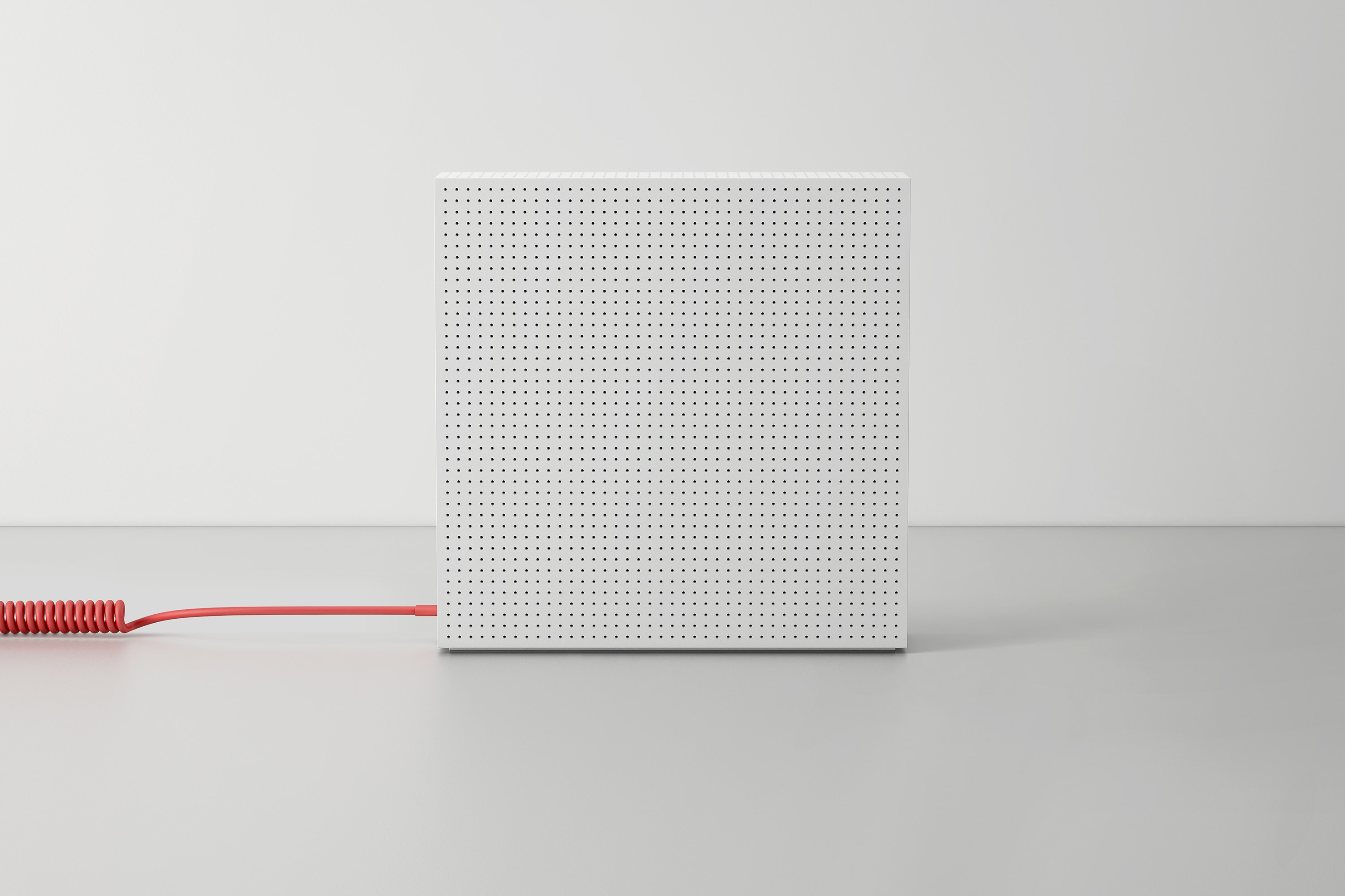 Side view of the DADI Node One in white with a red spiralled power cable plugged in on a grey surface.