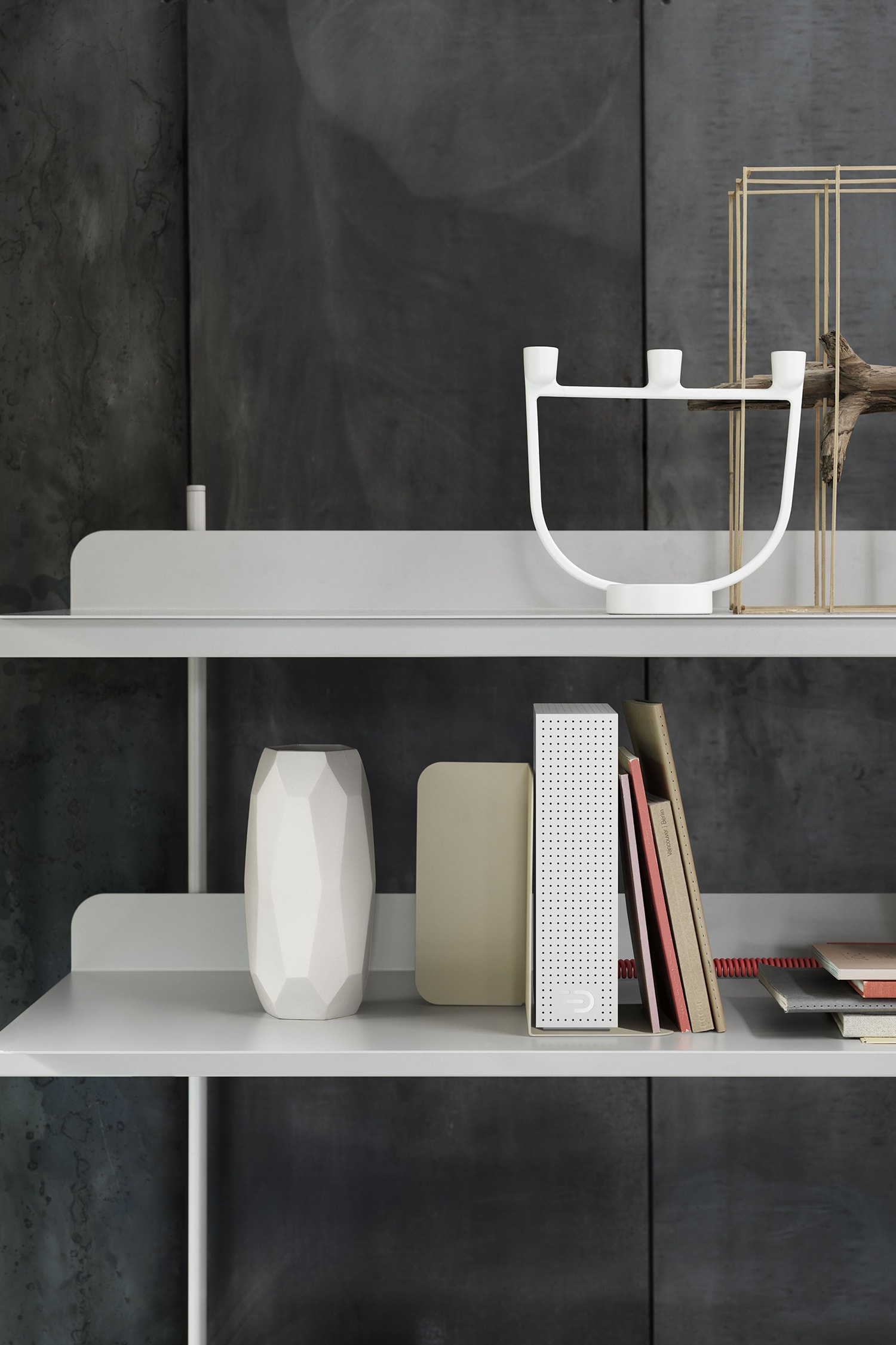 Front view of the Node one in white on a bookshelf beside other homeware objects such as a vase and candle holder. The casing is perforated with small holes for venting and shows the DADI logo.