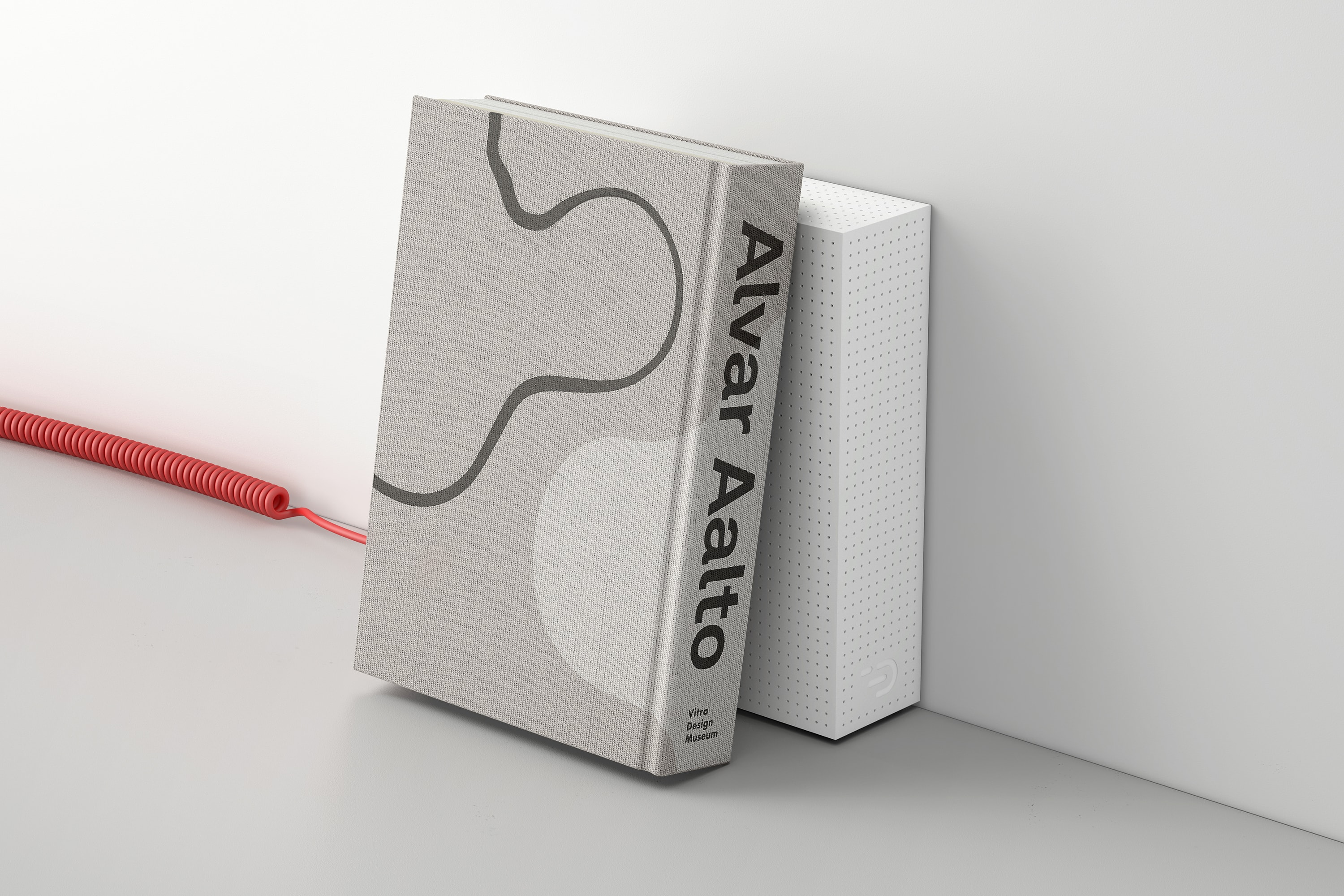 Perspective view of the Node one in white beside a Alvar Aalto book. The casing is perforated with small holes for venting and shows the DADI logo. The red spiralled power cable is plugged in.