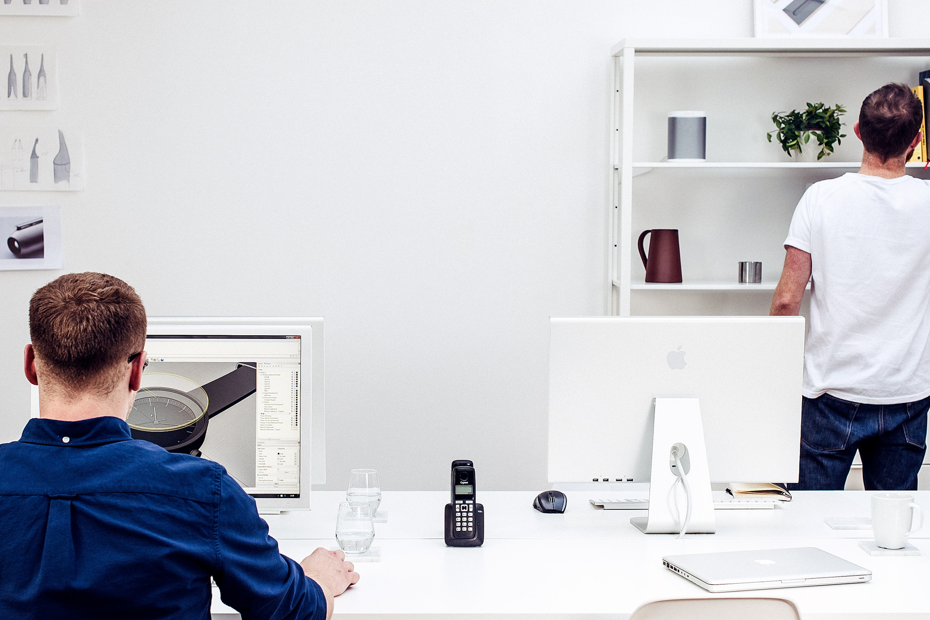 The image shows people working in a design studio. There are several computers on desks and a man working on CAD software. Another man is looking at the shelves in the bacground. the shelves have several objects on them such as a speaker, a jug, a plant. On the desk is a phone, laptop, mug and glasses filled with water. On the wall in the background are some sketches.