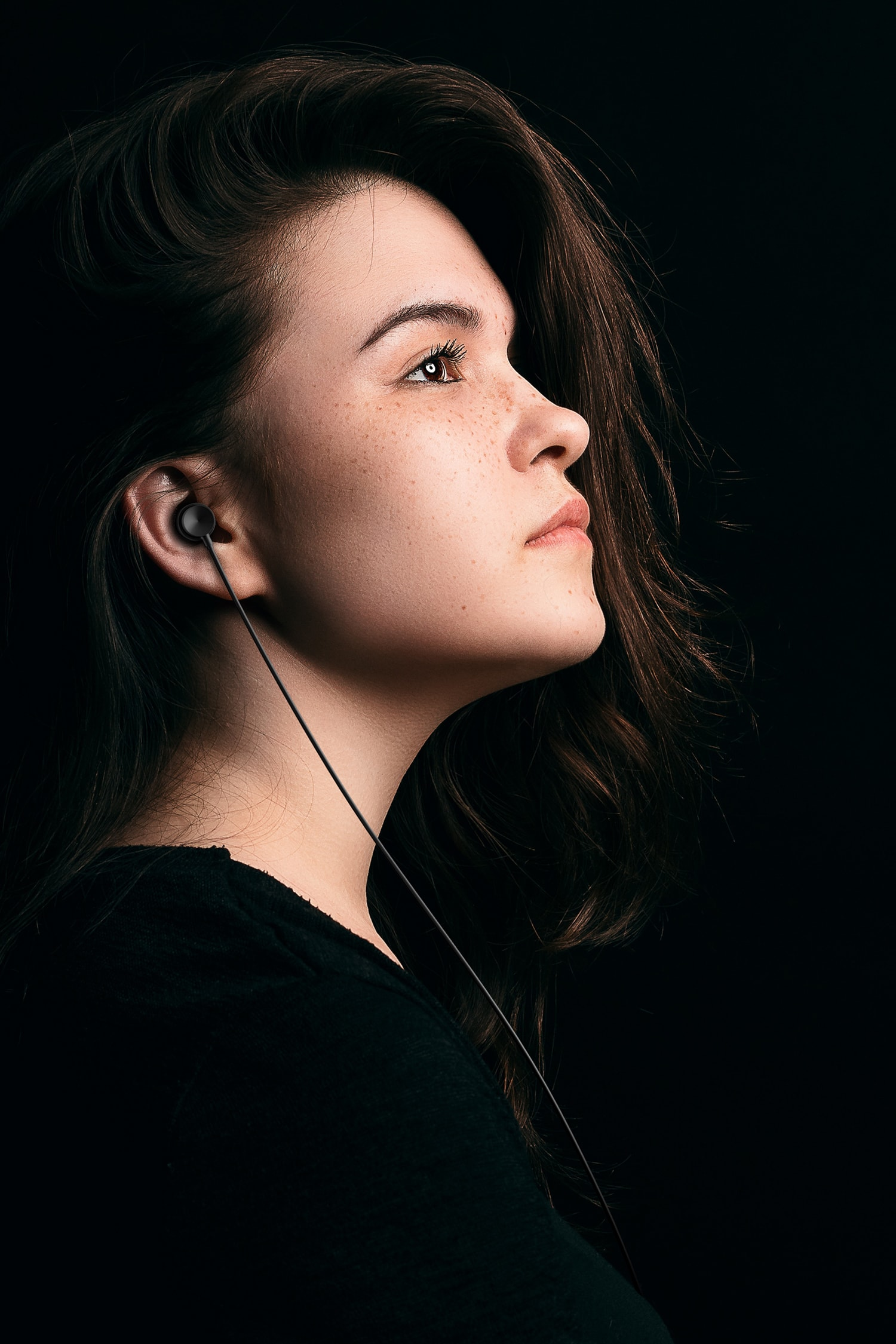 Black headphones in a young woman's ear.