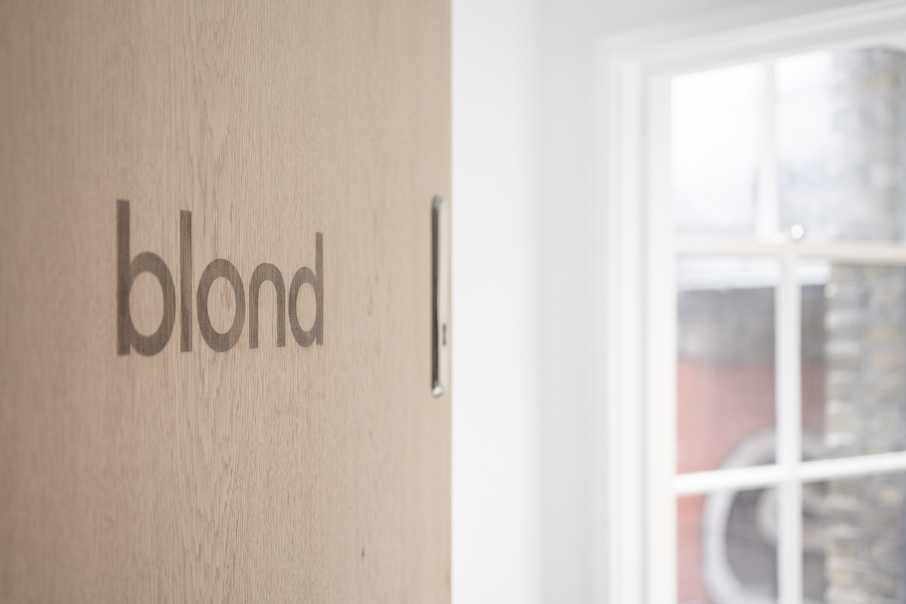 A partially open wooden door with the blond logo engraved. A window can be seen in the background.